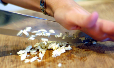 Mincing the garlic, rocking the knife blade by anchoring the tip with your palm
